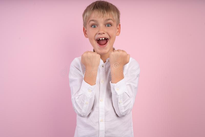 Young emotional handsome boy standing on pink studio background. Human emotions, facial expression concept stock photo