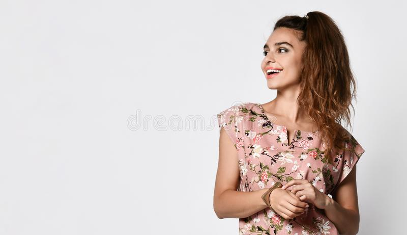 Young emotional long-haired woman posing in a new floral pink fashionable dress, happy full body smiles on a white background. royalty free stock photos