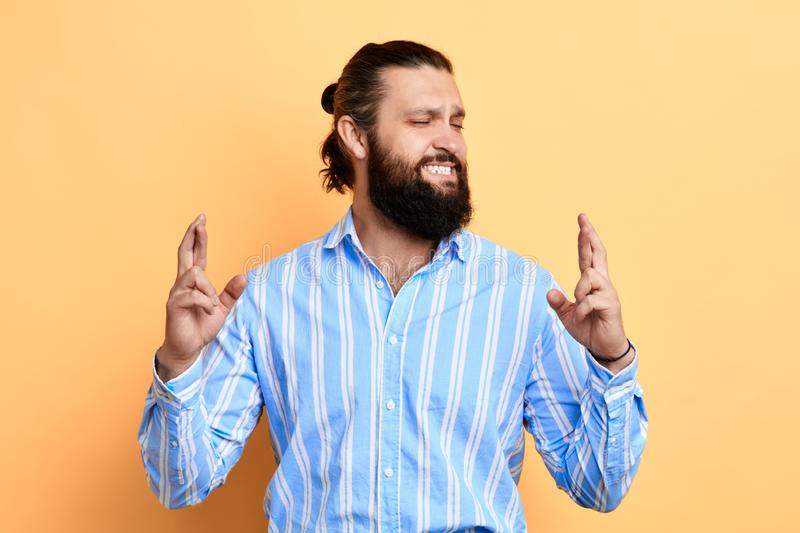 Young emotional man making a wish isolated on yellow background stock image