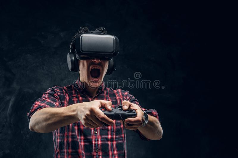 Emotional man using VR headset and playing a video game with joystick in a studio against the background of the dark stock photography