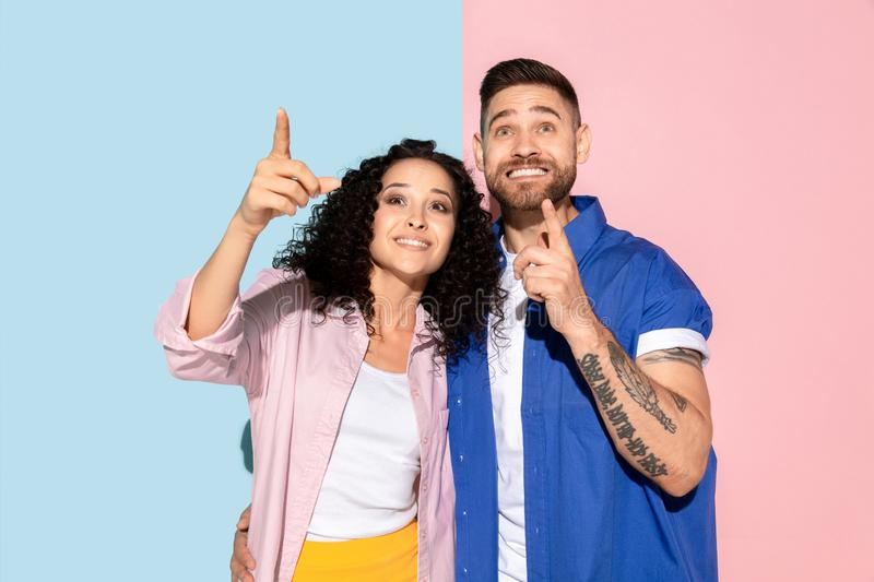 Young emotional man and woman on pink and blue background. Young emotional caucasian couple in bright casual clothes posing on pink and blue background. Concept royalty free stock photography