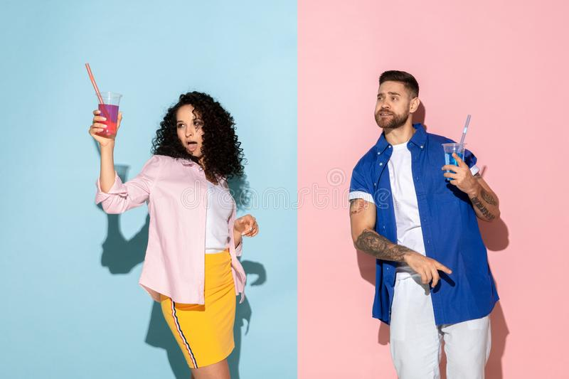 Young emotional man and woman on pink and blue background. Young emotional caucasian couple in bright casual clothes posing on pink and blue background. Concept royalty free stock images