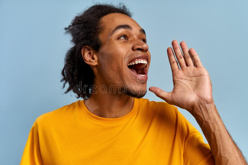 Young emotional mixed race guy screams substituting palm on blue background stock photos