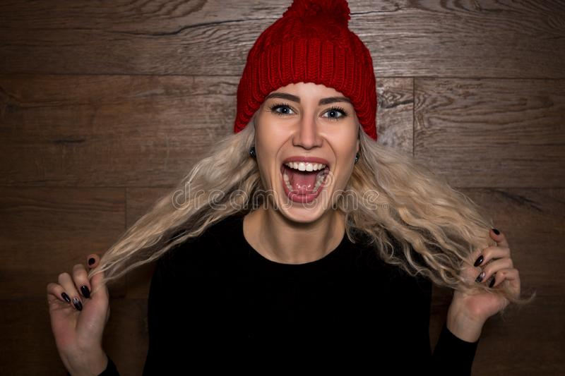 Young Emotional Woman Blonde in a Warm Cap with Long Hair royalty free stock photography