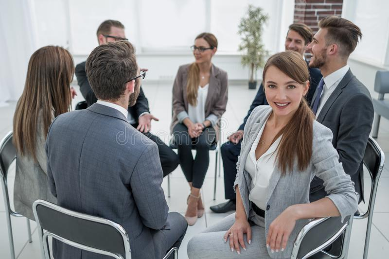 Young employee in the circle of like-minded business meeting royalty free stock image