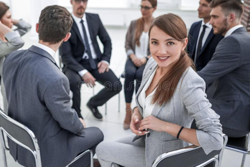 Young employee in the circle of like-minded business meeting stock photography
