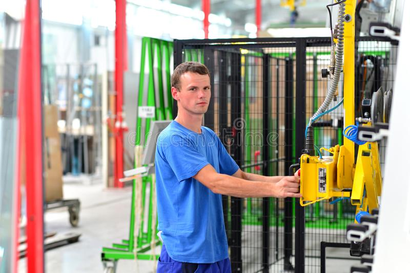 Young employee in a company manufacturing safety glass for house construction - works with a lifting tool stock photography