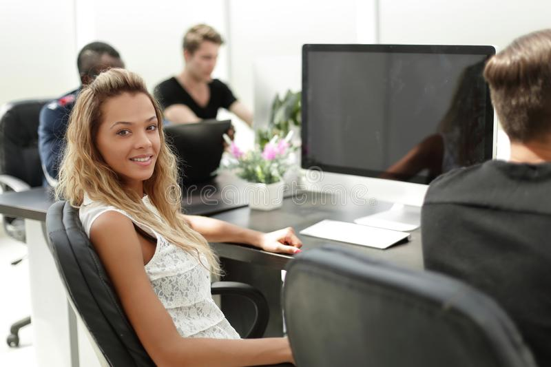 Young employee of the company sitting at his Desk. The concept of teamwork royalty free stock photos
