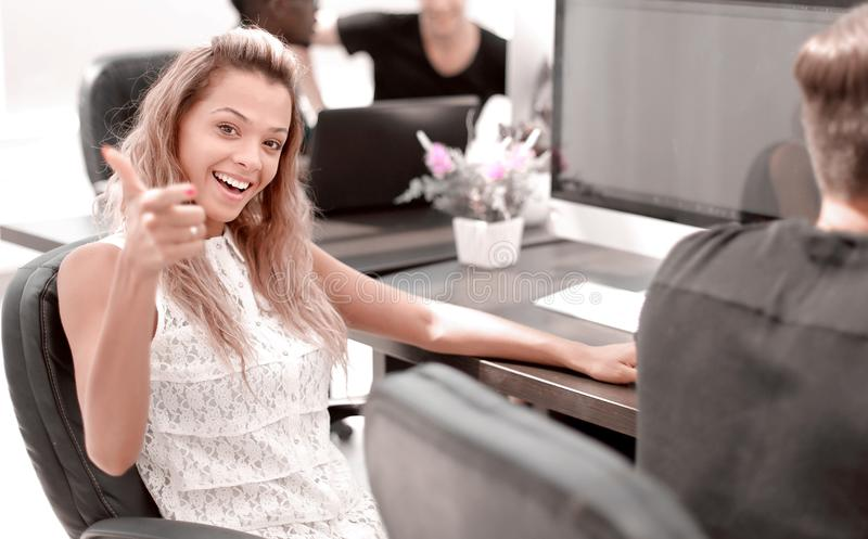 Young employee of the company sitting at his Desk and pointing at you. The concept of employment stock image