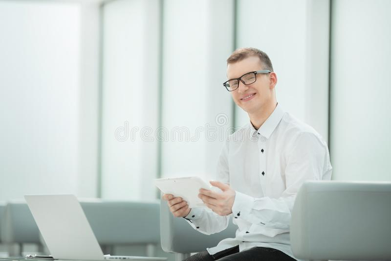 Young employee with a digital tablet sitting in a bright office. Photo with copy space royalty free stock photo