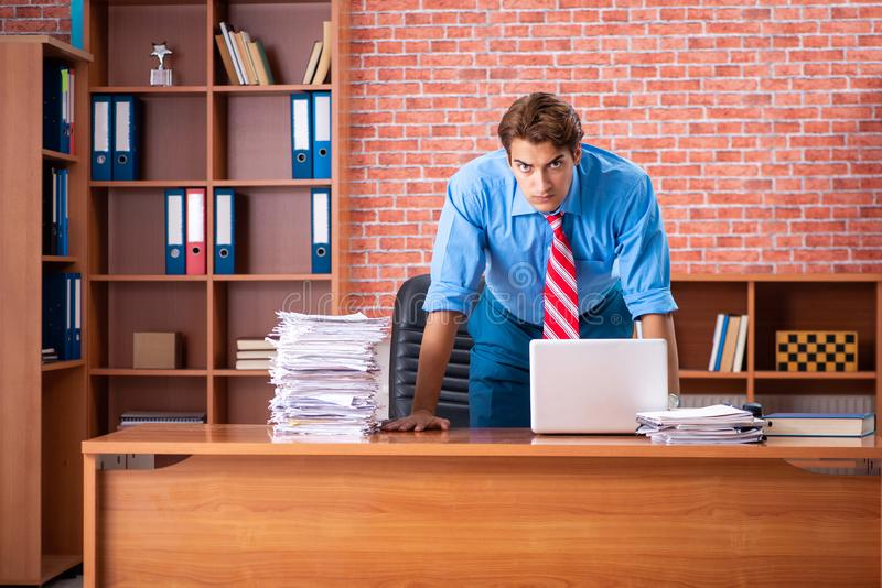 The young employee with excessive work sitting at the office. Young employee with excessive work sitting at the office stock photo