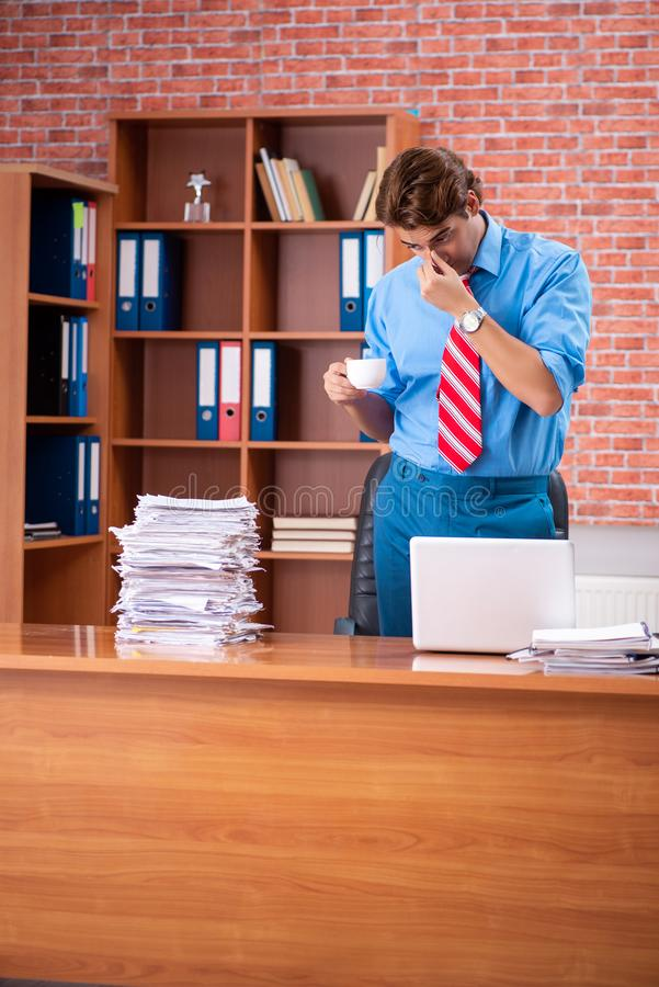 The young employee with excessive work sitting at the office. Young employee with excessive work sitting at the office stock images