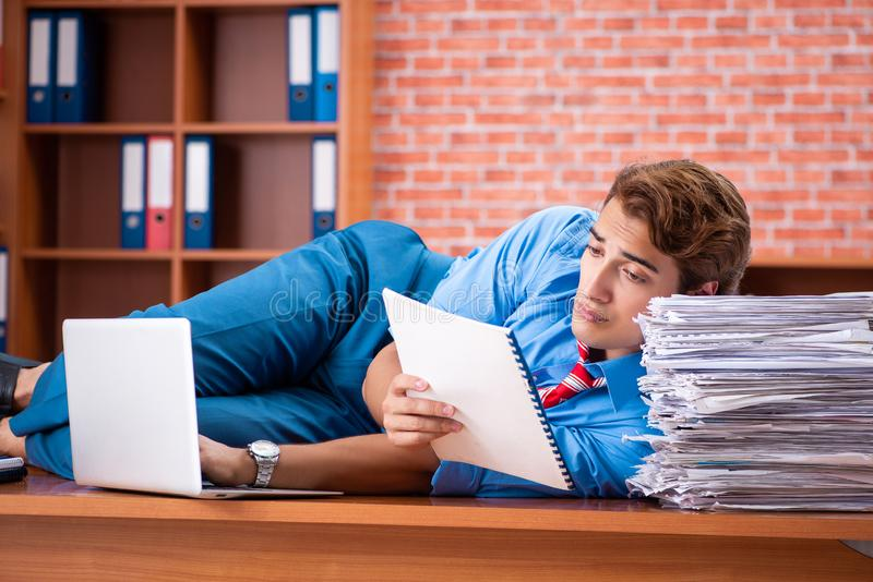 The young employee with excessive work sitting at the office. Young employee with excessive work sitting at the office stock photos