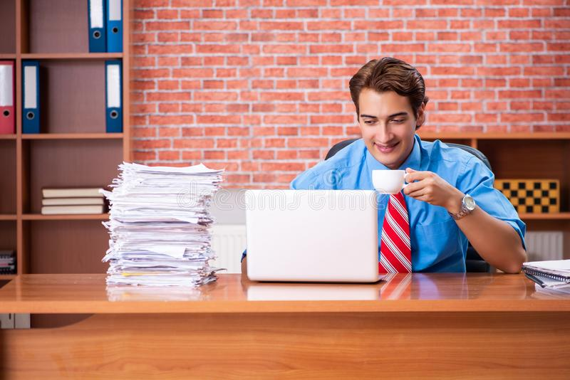 The young employee with excessive work sitting at the office. Young employee with excessive work sitting at the office royalty free stock images