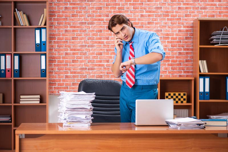 The young employee with excessive work sitting at the office. Young employee with excessive work sitting at the office stock photography
