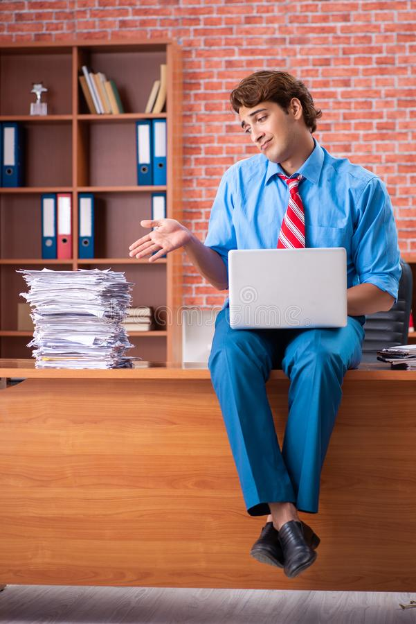The young employee with excessive work sitting at the office. Young employee with excessive work sitting at the office royalty free stock photography
