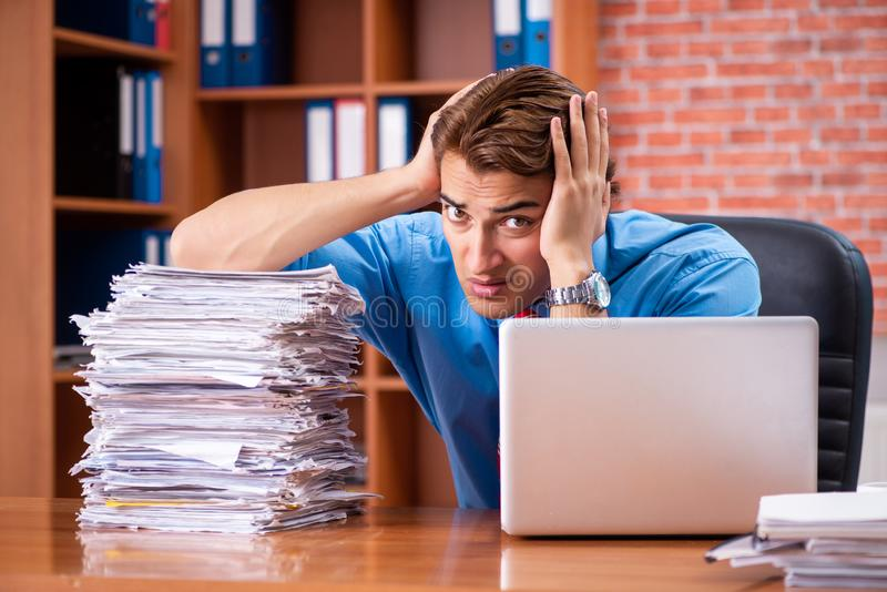 The young employee with excessive work sitting at the office. Young employee with excessive work sitting at the office royalty free stock photo