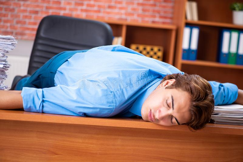 The young employee with excessive work sitting at the office. Young employee with excessive work sitting at the office royalty free stock photos