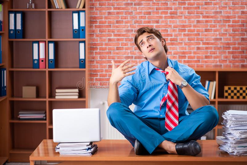 The young employee with excessive work sitting at the office. Young employee with excessive work sitting at the office stock image