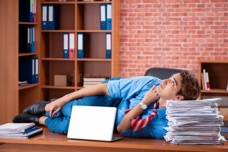 The young employee with excessive work sitting at the office. Young employee with excessive work sitting at the office royalty free stock image