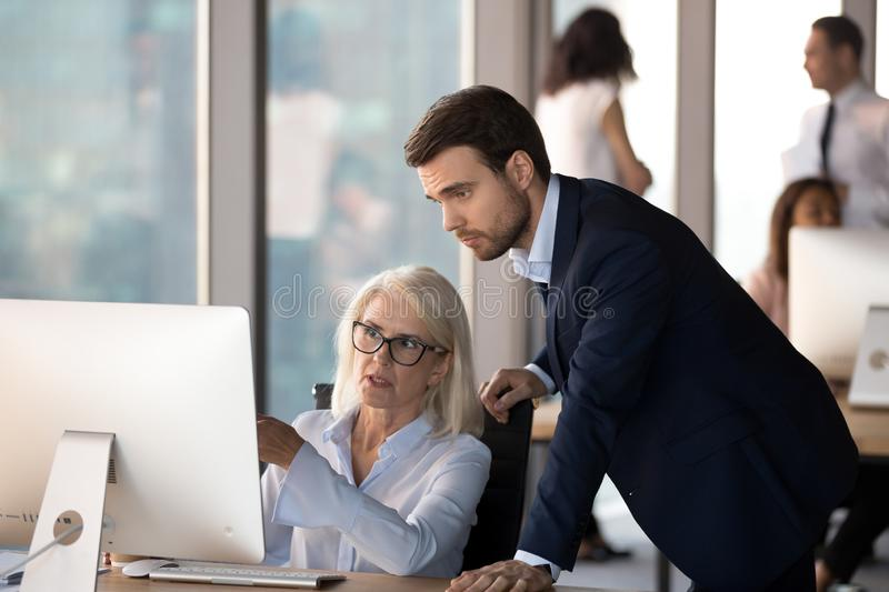 Young employee helps middle aged colleague learn corporate progr stock photos