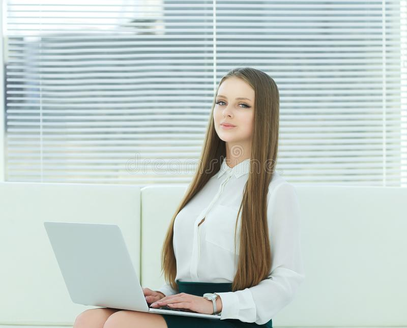 Young employee with a laptop sitting in the lobby of the office. Photo with place for text stock photography