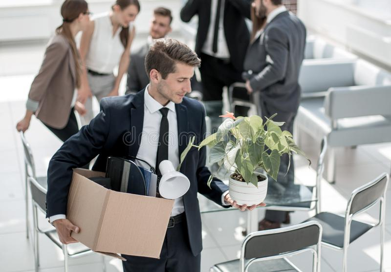 Young employee with personal things standing in the office stock image