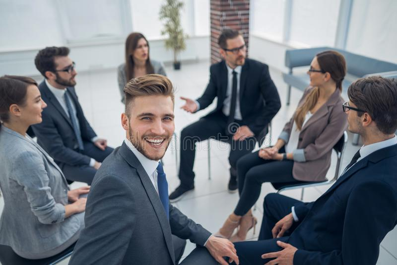 Young employee sitting in a circle with business team. The concept of team building stock photography