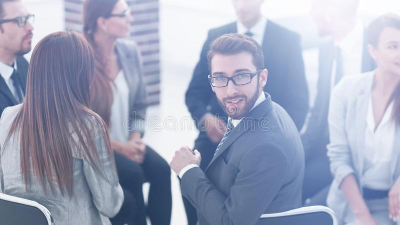 Young employee sitting in a circle of colleagues. And looking at the camera royalty free stock photography