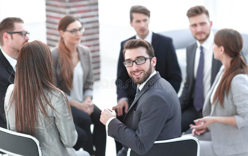 Young employee sitting in a circle of colleagues stock photos