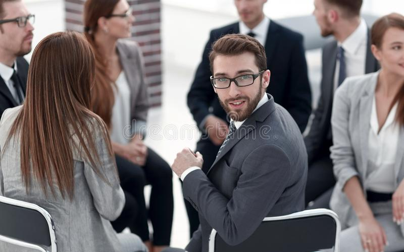 Young employee sitting in a circle of colleagues. And looking at the camera royalty free stock photos
