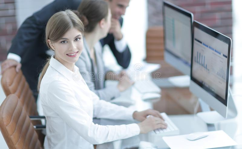 Young employee sitting at a Desk. E view. young employee sitting at a Desk and looking at camera stock image
