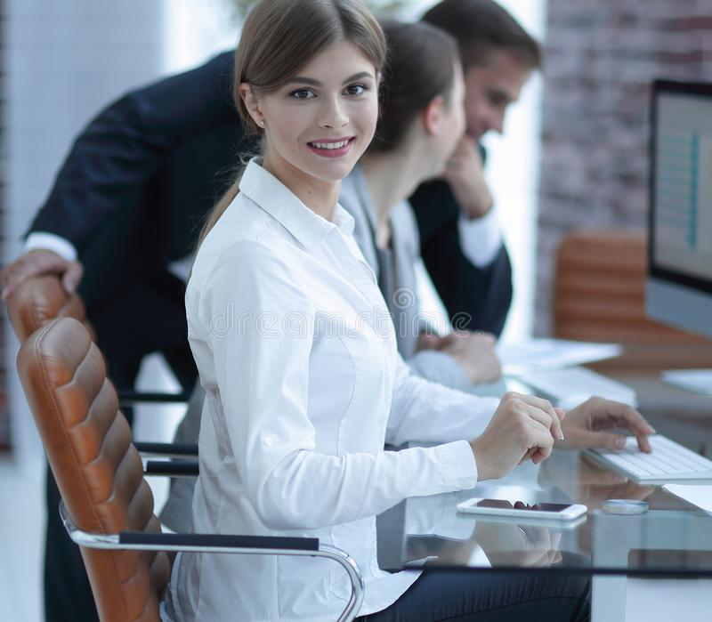 Young employee sitting at a Desk. E view. young employee sitting at a Desk and looking at camera stock photo