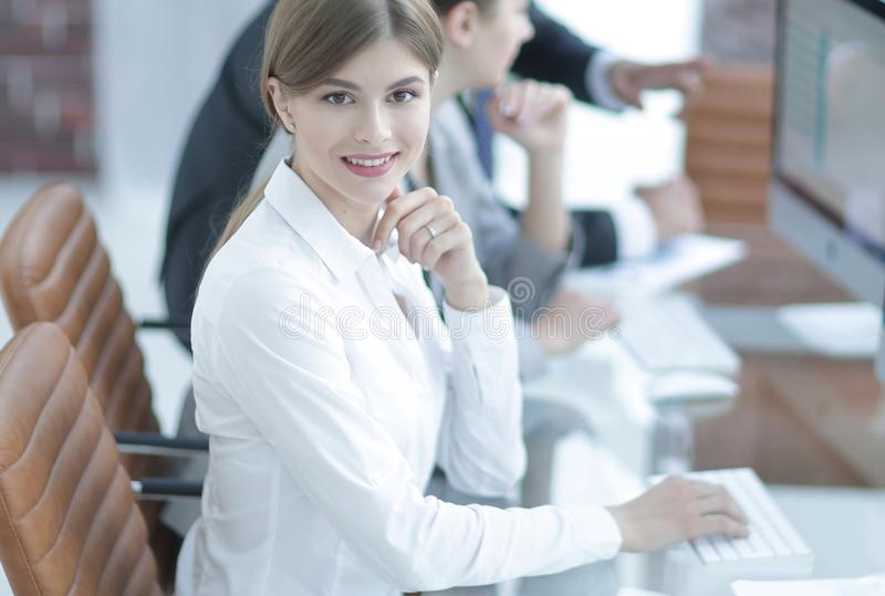 Young employee sitting at a Desk. Side view. young employee sitting at a Desk and looking at camera stock photo