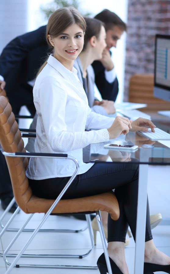 Young employee sitting at a Desk. Side view. young employee sitting at a Desk and looking at camera stock images