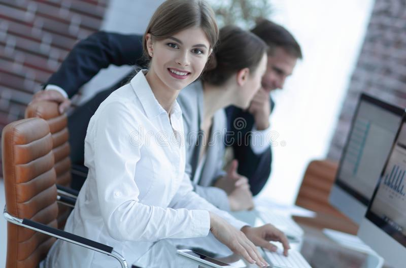 Young employee sitting at a Desk. Side view. young employee sitting at a Desk and looking at camera royalty free stock photography