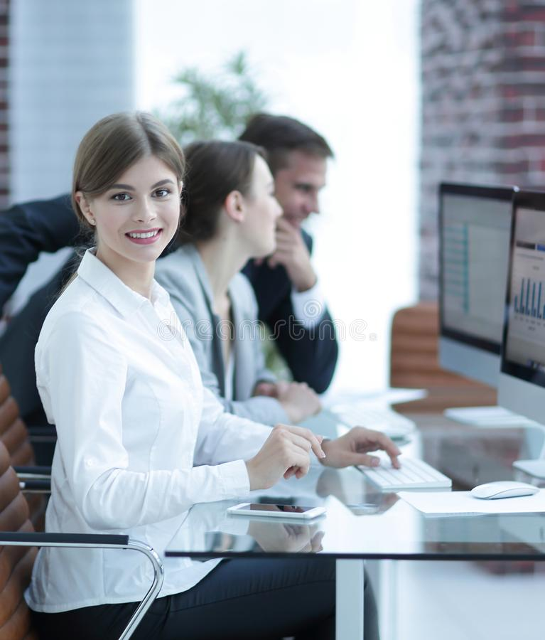 Young employee sitting at a Desk. Side view. young employee sitting at a Desk and looking at camera stock photography