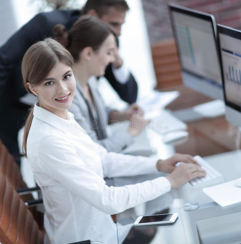 Young employee sitting at a Desk. Side view. young employee sitting at a Desk and looking at camera stock photos