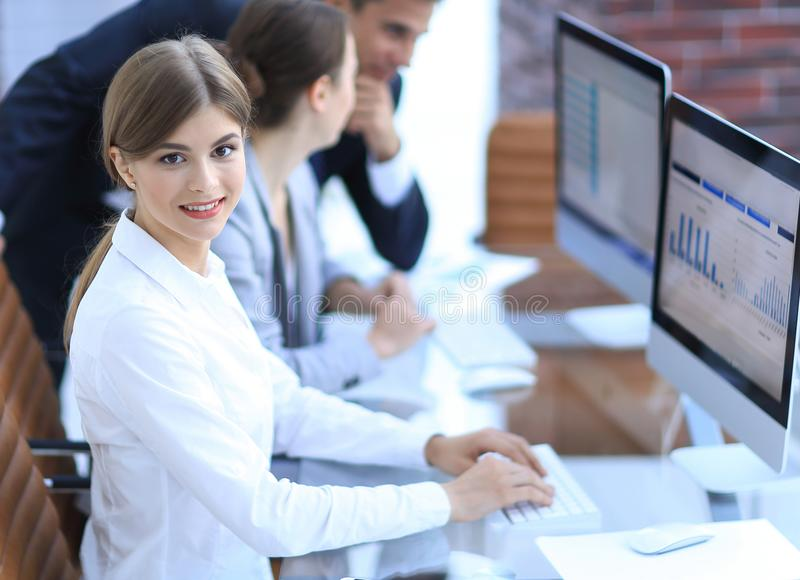 Young employee sitting at a Desk. Side view. young employee sitting at a Desk and looking at camera stock image