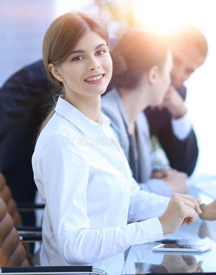 Young employee sitting at a Desk. Side view. young employee sitting at a Desk and looking at camera royalty free stock photo