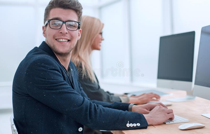 Young employee sitting at his Desk in the office royalty free stock photography