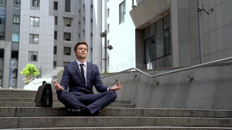 Young employee sitting in lotus position, abstracting from everyday stresses. Stock photo stock photo