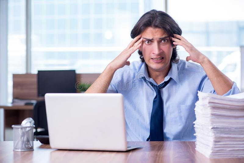 Young employee unhappy with excessive work stock photo