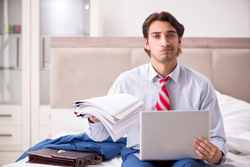 The young employee working at home sitting on the bed. Young employee working at home sitting on the bed royalty free stock images