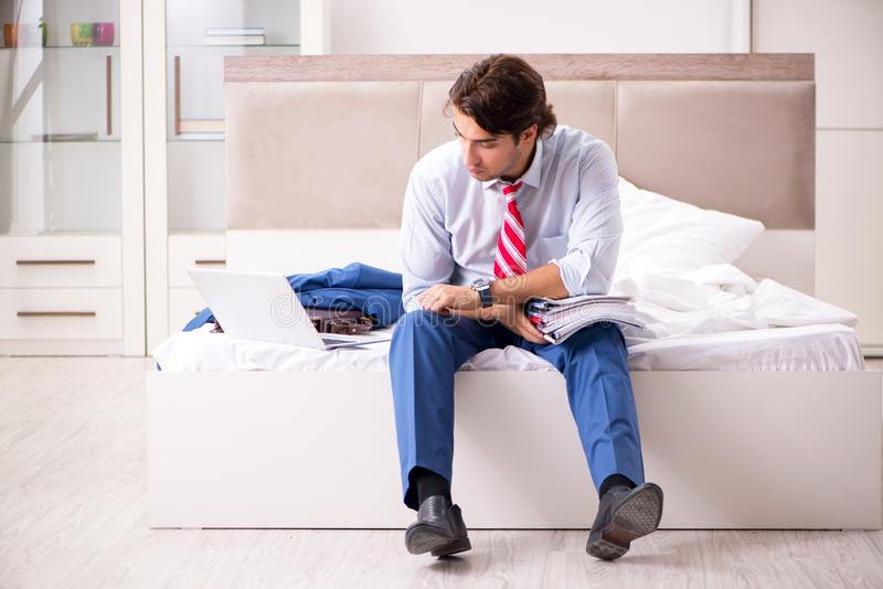 The young employee working at home sitting on the bed. Young employee working at home sitting on the bed royalty free stock image