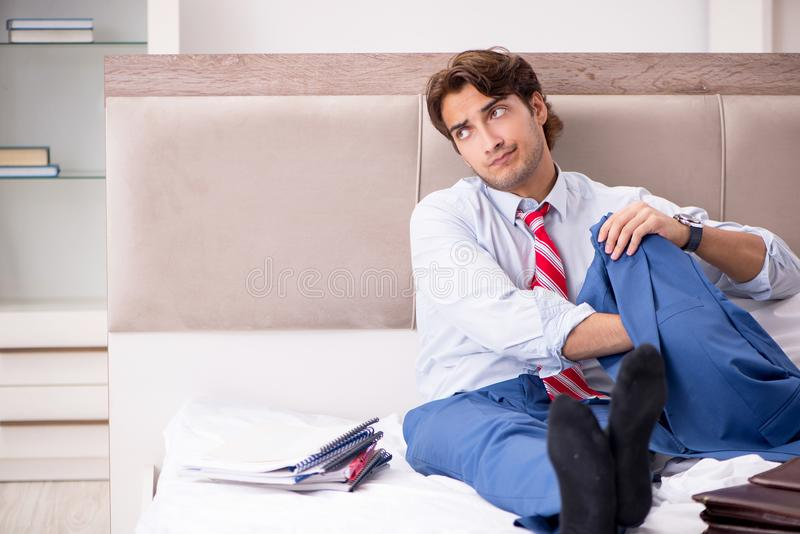 The young employee working at home sitting on the bed. Young employee working at home sitting on the bed royalty free stock photography