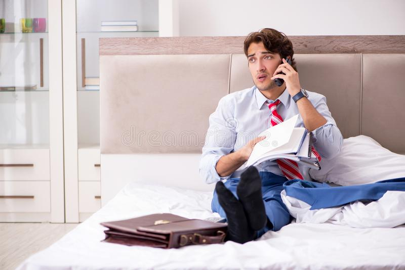 The young employee working at home sitting on the bed. Young employee working at home sitting on the bed stock photo