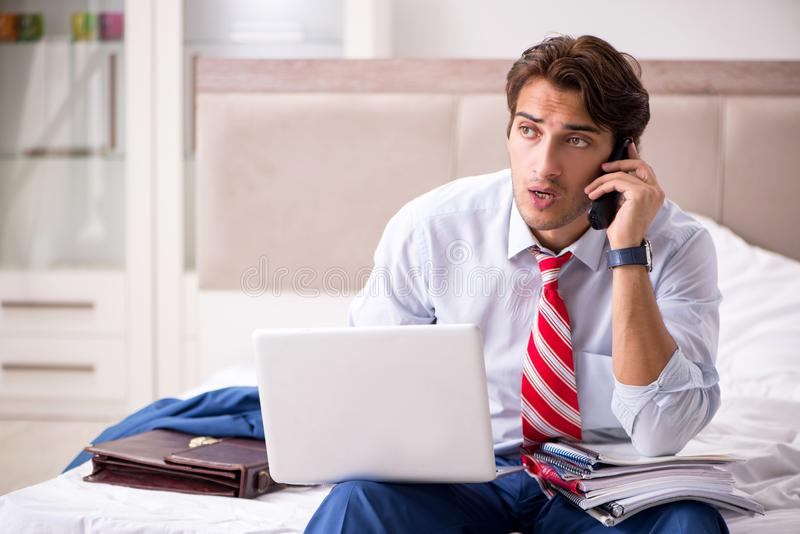 The young employee working at home sitting on the bed. Young employee working at home sitting on the bed stock image
