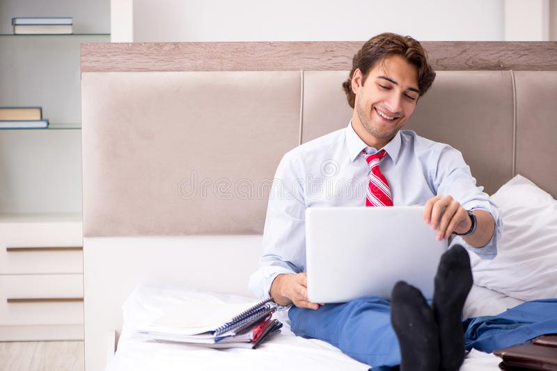 The young employee working at home sitting on the bed. Young employee working at home sitting on the bed stock images