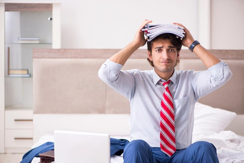 The young employee working at home sitting on the bed. Young employee working at home sitting on the bed stock photos